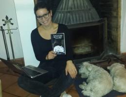Ghaan Ima, une fille à lunettes tient un bouquin à la main assise devant une cheminée avec des chiens tout crados à côté