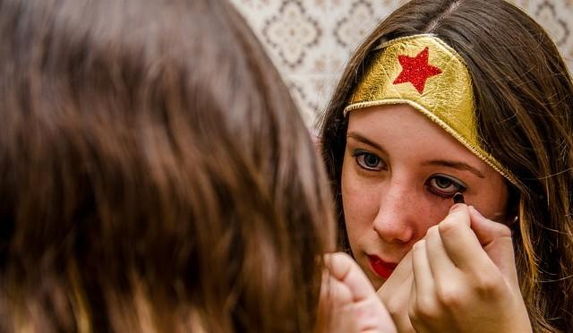 une femme se maqueille avec sur la tête le bandeau doré de wonder woman