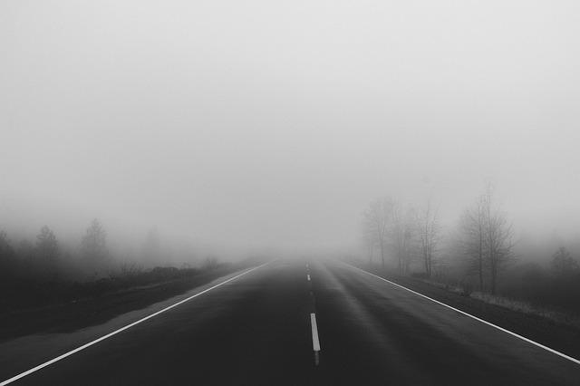 une route droite et vide qui conduit dans le brouillard, terne
